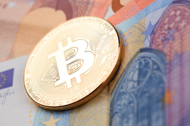 Złote bitcoiny ułożone na tle banknotów euro.
