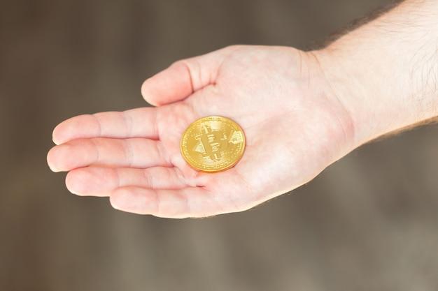 Złote bitcoiny w dłoni mężczyzny