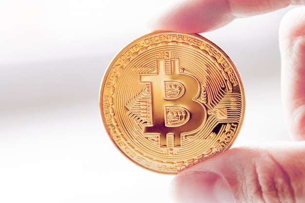 Złote bitcoiny w dłoni