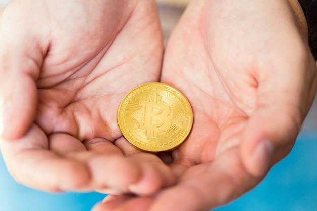 Złote bitcoiny w rękach