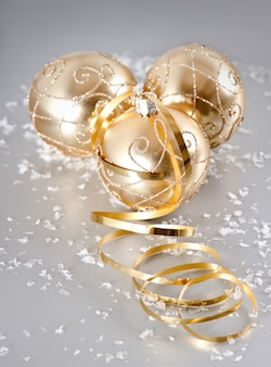 Złote błyszczące bombki ze śnieżną dekoracją na srebrnym tle