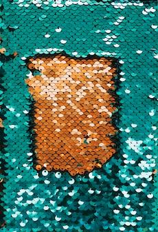 Złote błyszczące cekiny otoczone zielonymi odblaskowymi cekinami