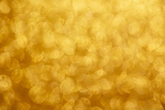 Złote błyszczące lampki świąteczne. niewyraźne tło.