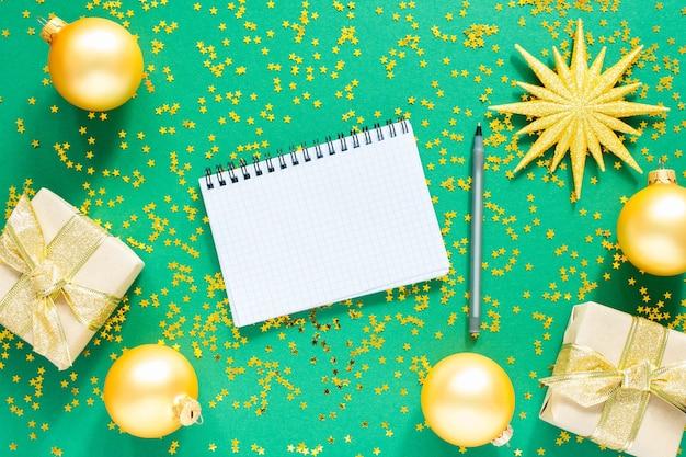 Złote bombki i gałązki jodłowe oraz jasna błyszcząca świąteczna girlanda na zielonej powierzchni z brokatowymi złotymi gwiazdami, otwarty spiralny notatnik i długopis, płaskie ułożenie, widok z góry