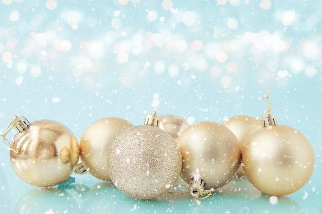 Złote bombki na śniegu z delikatnym bokeh na jasnoniebieskim tle.