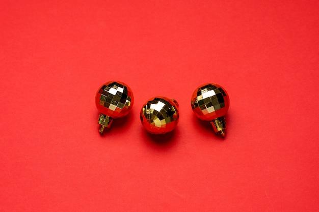 Złote bombki świąteczne dekoracje na czerwonym tle.