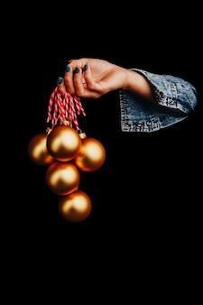 Złote bombki w ręce kobiety na białym na czarnym tle