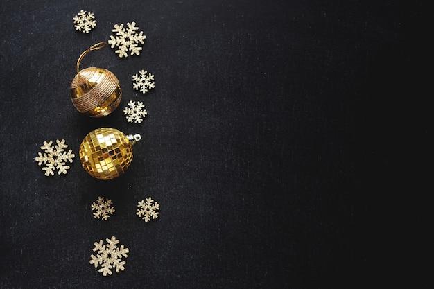 Złote bombki ze złotymi płatkami śniegu na ciemnym tle. koncepcja bożego narodzenia.