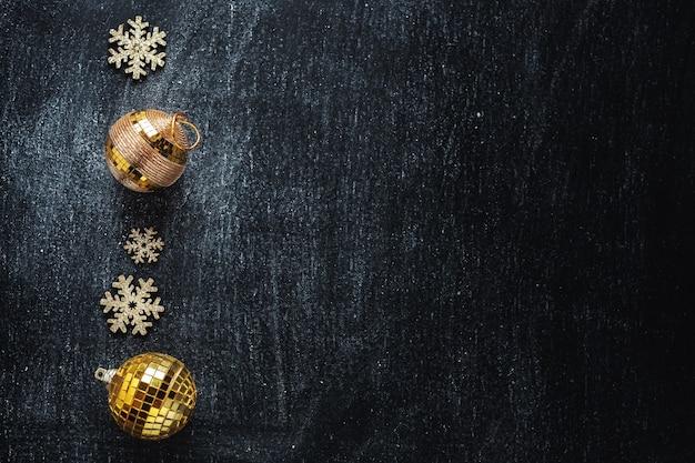 Złote bombki ze złotymi płatkami śniegu na czarnym tle. flat lay.