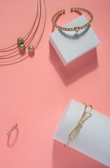 Złote bransoletki, naszyjnik i pierścionek ustawione na różowym i białym tle