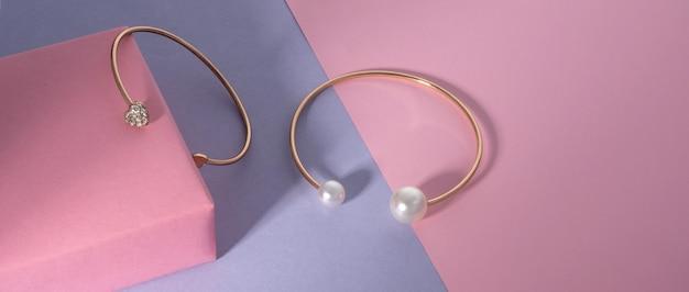 Złote bransoletki z kamieniami szlachetnymi na różowym i fioletowym tle z kopią miejsca