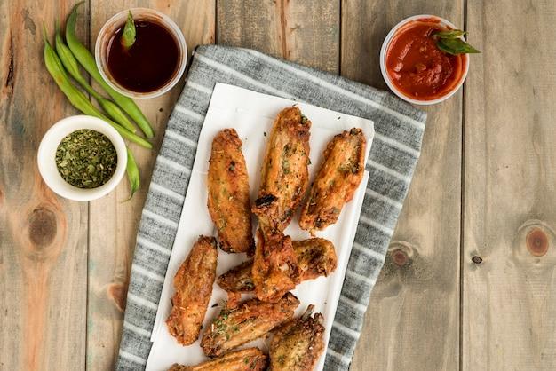 Złote brązowe pieczone skrzydełka z kurczaka i sosy