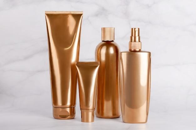 Złote butelki, kosmetyki na marmurowej powierzchni