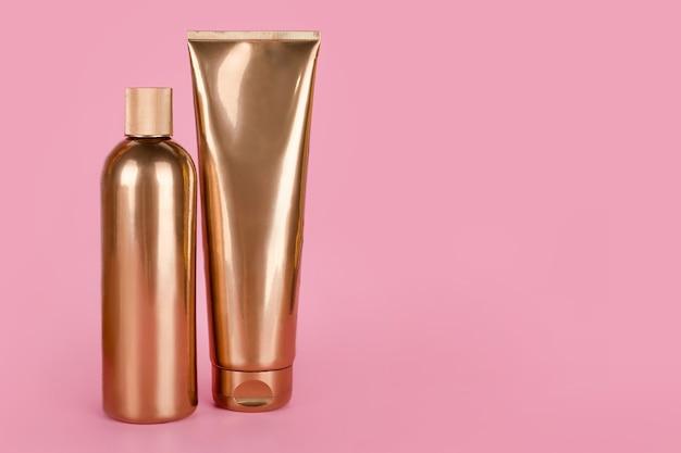 Złote butelki, kosmetyki na różowej powierzchni