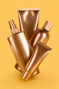 Złote butelki, kosmetyki na żółtej powierzchni