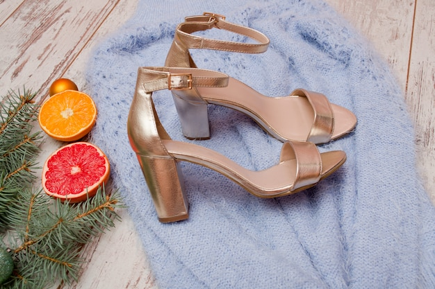 Złote buty na niebieskim swetrze, grejpfrutowym, pomarańczowym i świerkowym. koncepcja mody