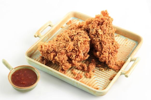 Złote chrupiące smażone piersi z kurczaka i skrzydełka kurczaka, podawane na rustykalnej kwadratowej płytce z sosem chili, izolowana na białym tle z miejscem kopiowania tekstu