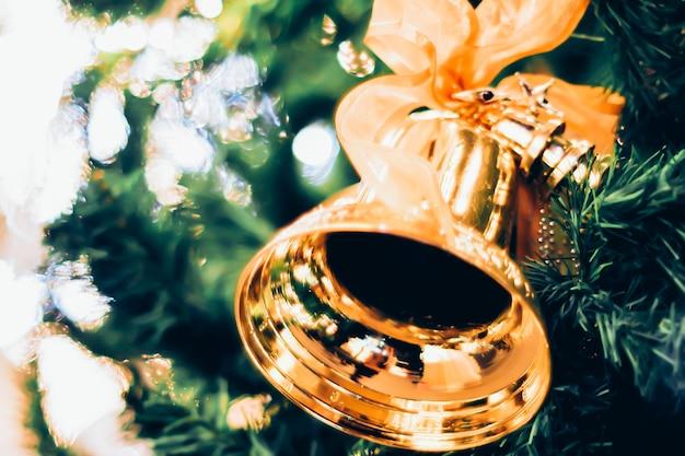 Złote dzwonki z czerwoną kokardą na choince rozmywają jasne tło bokeh