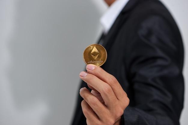 Złote etherium w dłoni mężczyzny, symbol digitall nowej wirtualnej waluty