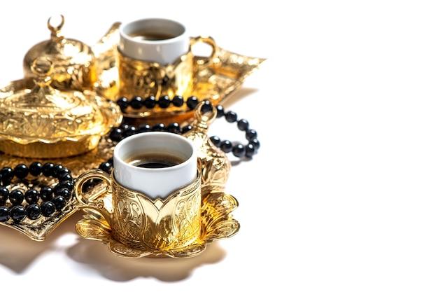 Złote filiżanki do kawy i różaniec. święta islamskie. ramadan kareem