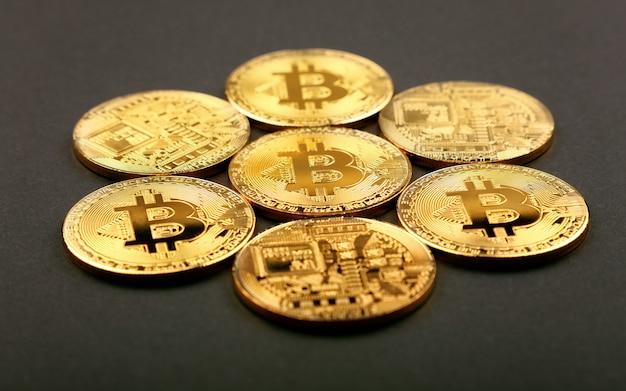 Złote fizyczne monety bitcoin na czarno
