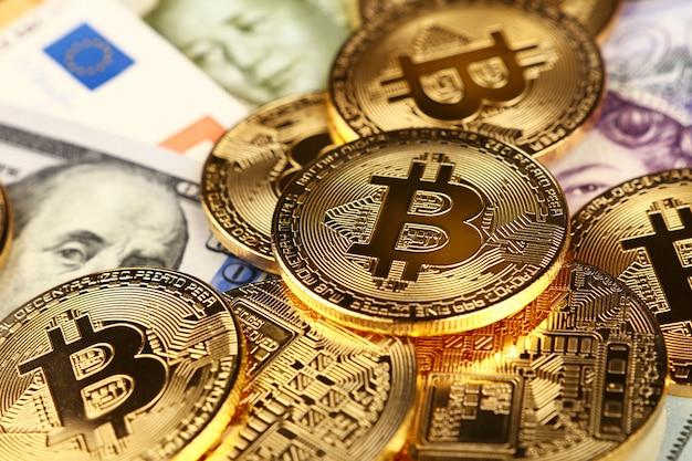 Złote fizyczne monety bitcoin na papierowej walucie