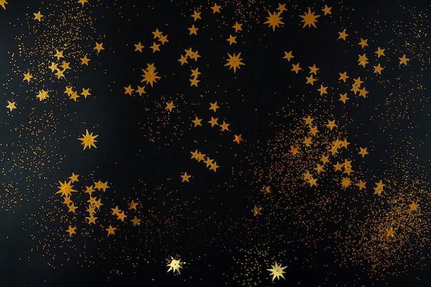 Złote gwiazdy na czarnym tle. leżał płasko, widok z góry.