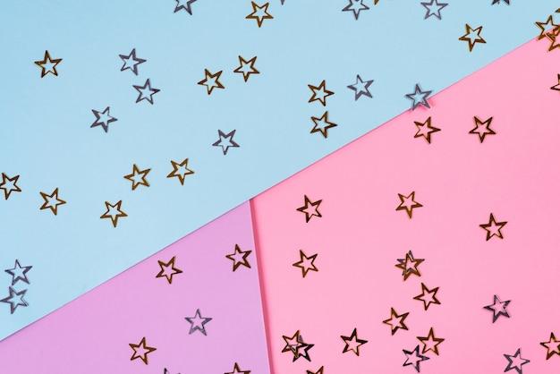 Złote gwiazdy na różowym niebieskim tle. motyw urodzinowy lub imprezowy. minimalna koncepcja. leżał płasko. widok z góry.