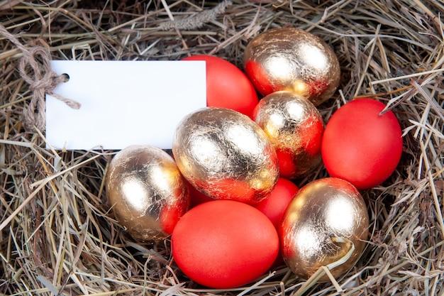 Złote i czerwone jajka w gnieździe. koncepcja wielkanocna. makieta