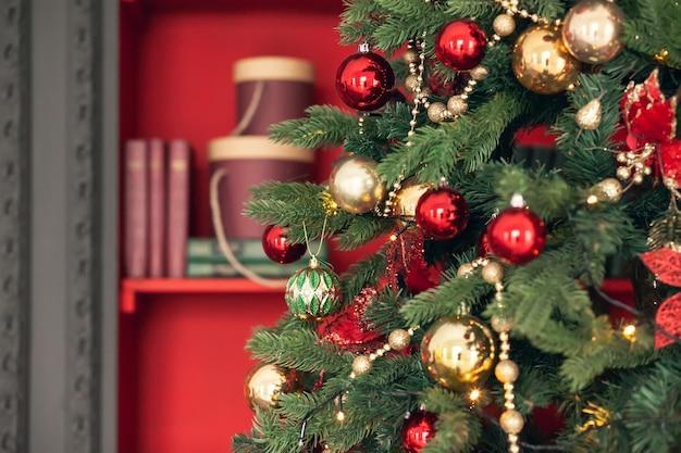 Złote i czerwone zabawki świąteczne, kulki, girlandy na gałęzi świerkowej na ciemnoczerwonym tle.
