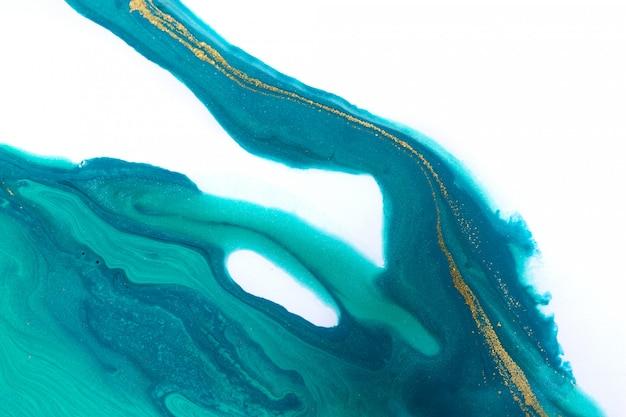 Złote i niebieskie farby mieszane rozpryskiwane na tle białego papieru.