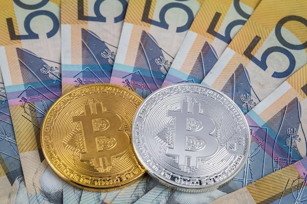 Złote i odłamkowe bitcoiny na stosie australijczyków 50 dolarów banknotów zbliżenie
