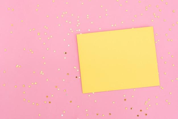 Złote i różowe konfetti wylanie z białej koperty na pastelowym różowym tle.