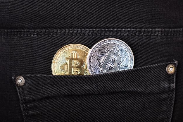 Złote i srebrne bitcoiny w twojej kieszeni zbliżenie. wzrost wartości kryptowalut.