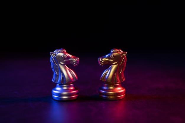 Złote i srebrne figury szachowe koń zaproś twarzą w twarz i w tle znajdują się figury szachowe. koncepcja rywalizacji, przywództwa i wizja biznesowa dla wygranej w grach biznesowych