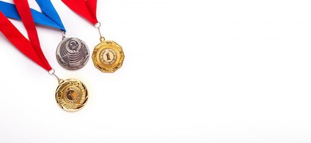 Złote i srebrne medale ze wstążką na białym tle.
