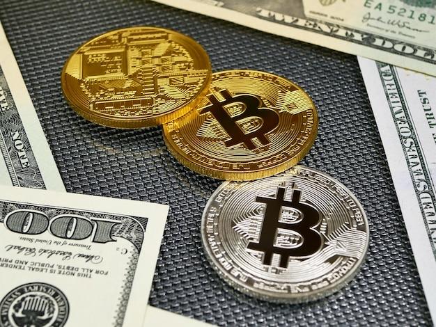 Złote i srebrne monety bitcoin oraz banknoty dolarów amerykańskich o abstrakcie.