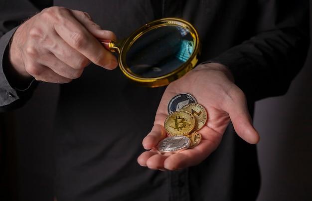 Złote i srebrne monety kryptowaluty w męskiej dłoni z lupą, z bliska. stos bitcoinów i innych kryptowalut.