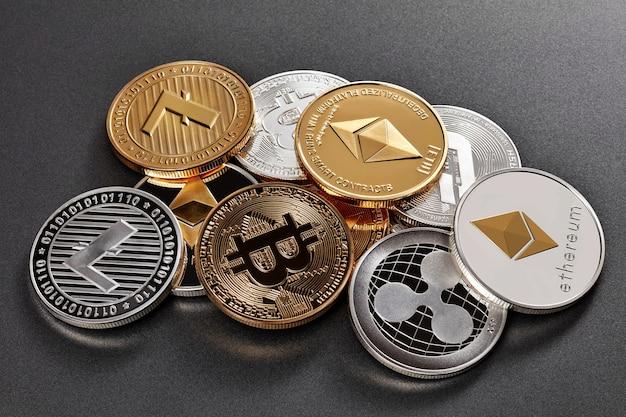 Złote i srebrne monety różnych kryptowalut na ciemnym tle. koncepcja kryptowalut i blockchain.