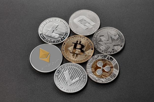 Złote i srebrne monety to monero, ripple, bitcoin, litecoin, ethereum, kreska, na czarnym tle. koncepcja handlu kryptowalutami i blockchain. widok z góry