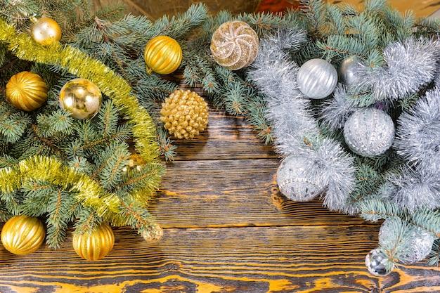 Złote i srebrne ozdoby świąteczne na gałęziach sosny ułożone w dwóch osobnych kolorach w rogach na rustykalnym drewnianym tle z copyspace pomiędzy, widok z góry