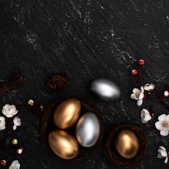 Złote i srebrne pisanki z kwiatem śliwki na ciemnym czarnym tle stołu łupkowego.