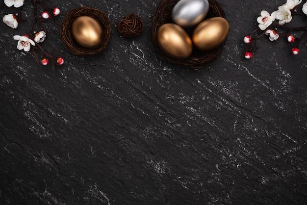 Złote i srebrne pisanki z kwiatem śliwki na tle łupków tabeli.
