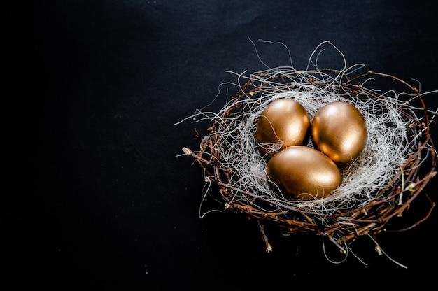 Złote jaja wielkanocne gniazdo na czarnym tle. ferie wielkanocne