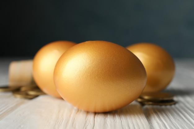 Złote jajka i pieniądze na drewnianej powierzchni
