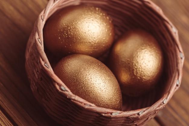 Złote jajka na drewnianym stole