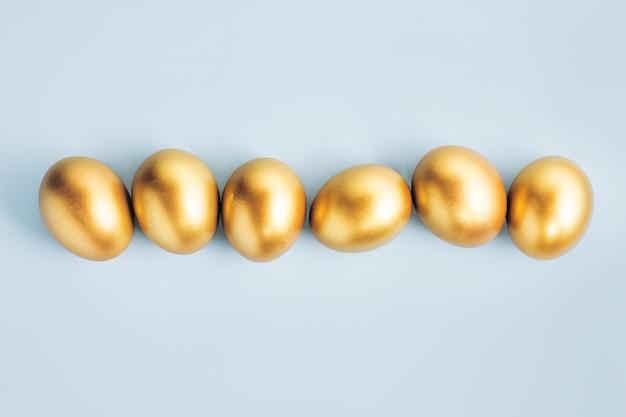 Złote jajka na niebieskim pastelowym stole