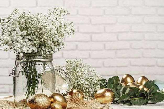 Złote jajka na wielkanocną kompozycję z kwiatowymi gałęziami