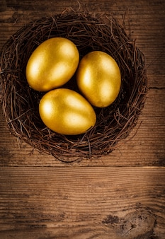 Złote jajka w gnieździe na drewnianym tle z kopią tekstu
