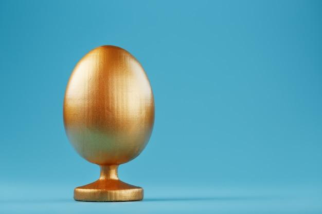 Złote jajko na niebieskim tle z minimalistyczną koncepcją. miejsce na tekst. szablony projektów pisanek. stylowy wystrój z minimalną koncepcją.